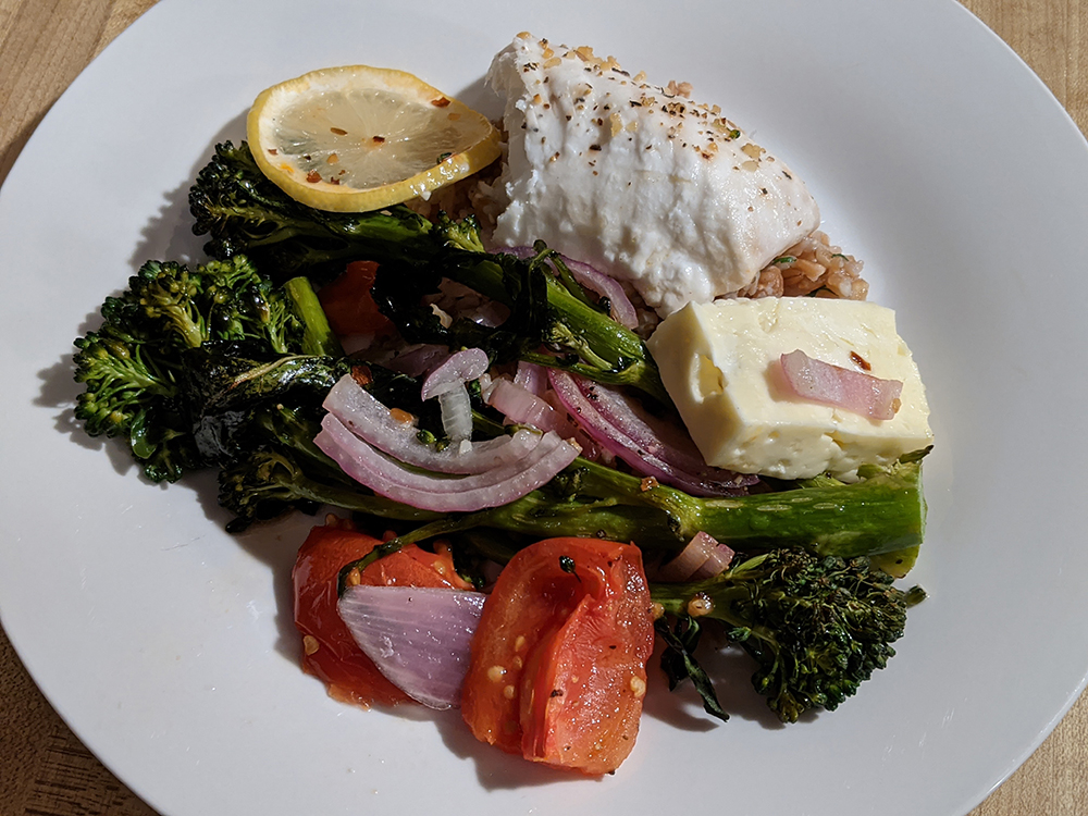 Baked feta, halibut, broccolini, onions, tomatoes, and lemons served over farro