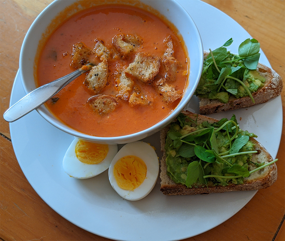 Tomato soup with sourdough croutons, avocado toast with pea shots, and a hard boiled egg